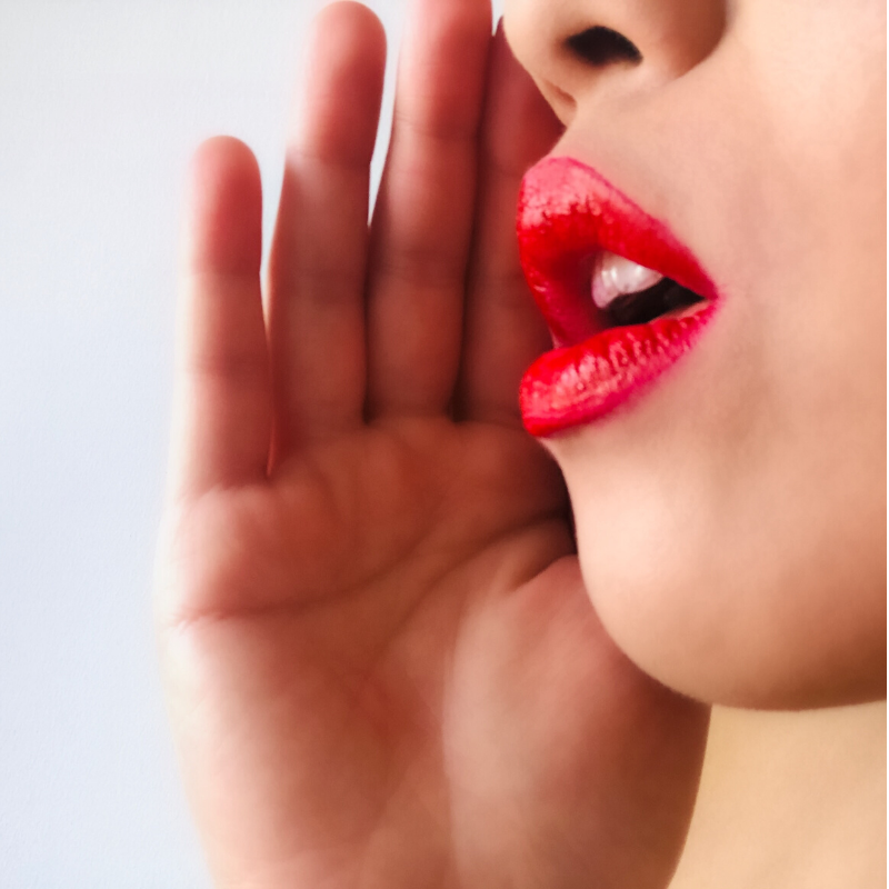 Woman with red lipstick whispering